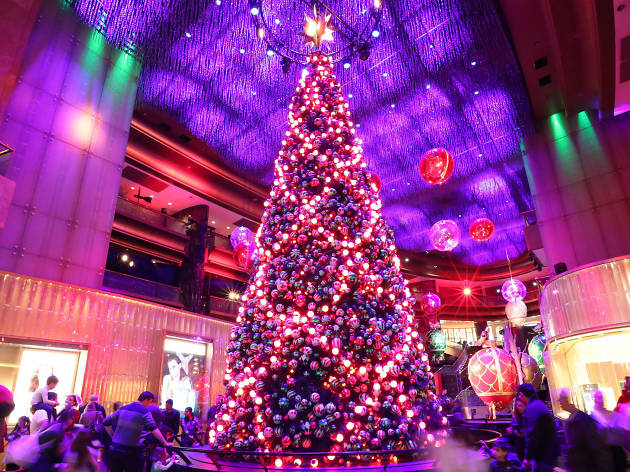 An oversized christmas tree covered in baubles and lights in the middle of Crown's atrium