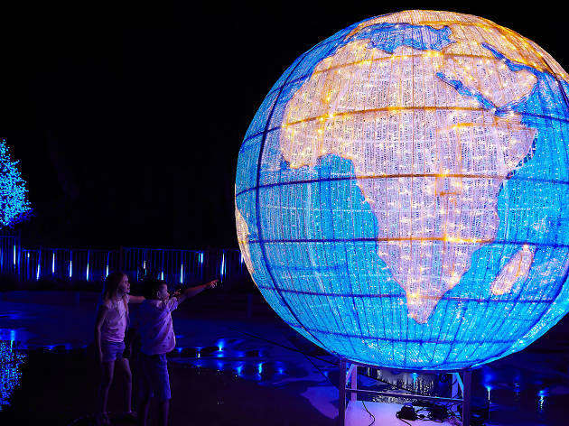 A giant glowing globe with two children looking at it