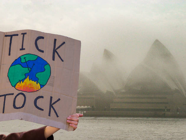 A person holds up a sign in front of the Sydney Opera House, which is blanketed in smoke, reading 'Tick Tock' with a painting of the earth in flames.