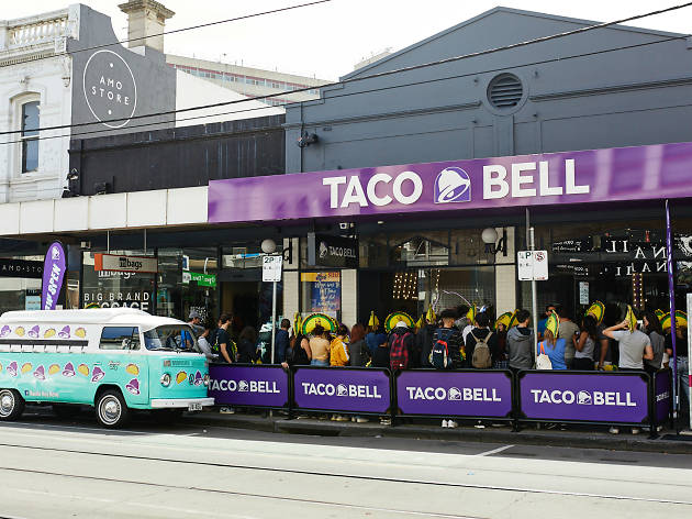 Outside the first taco bell in Victoria. There is a combi van on the street in front of the store and people wearing taco hats lining up outside.