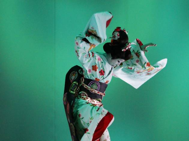A performer in traditional Kabuki costume dances in front of a turquoise background.