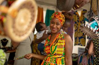 A woman wearing traditional African printed dress and turban smiles.