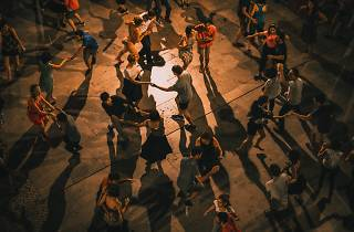 A dimly lit dance floor of people are dancing.
