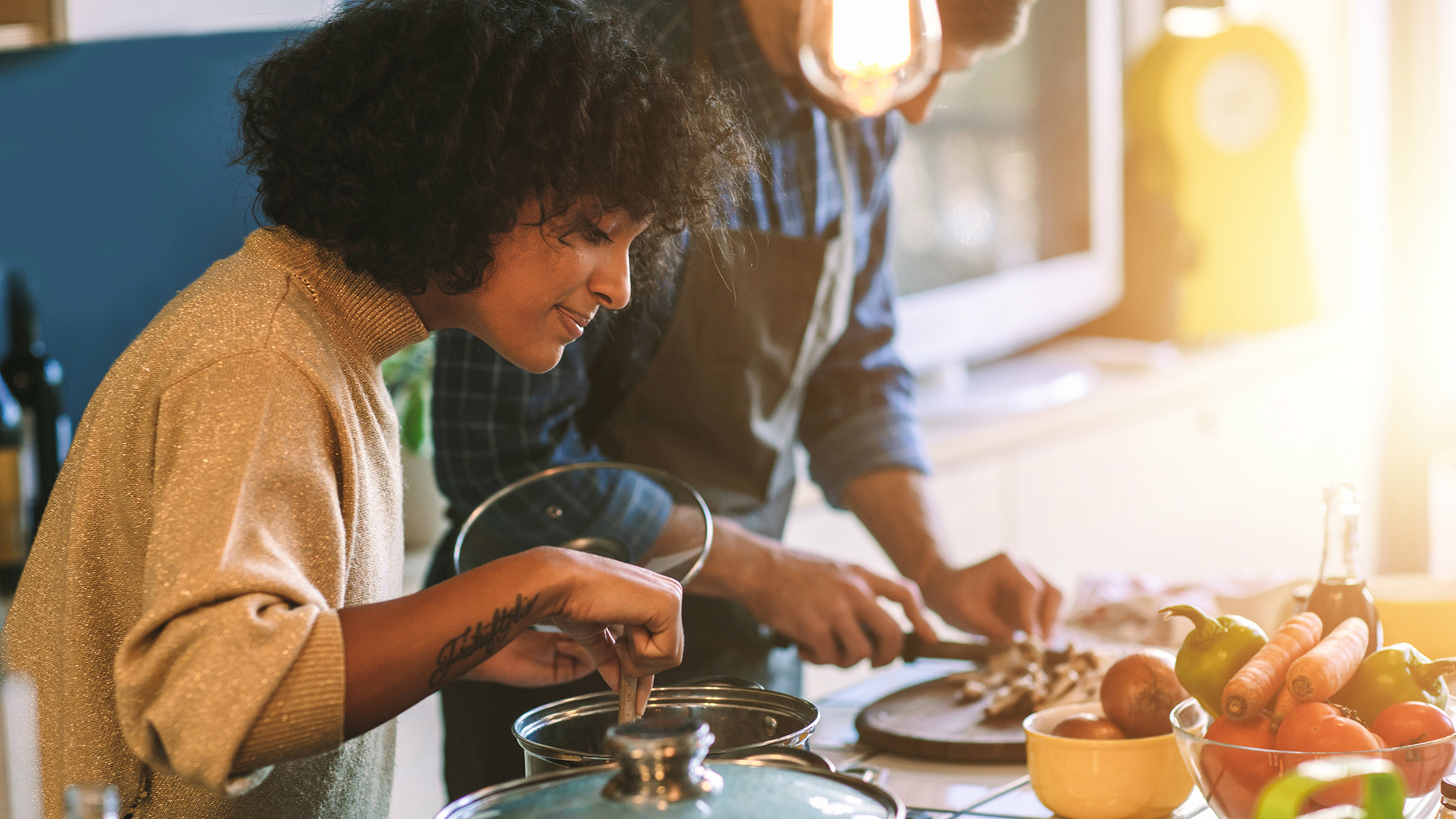 Woman and man standing over stove stirring pots of food