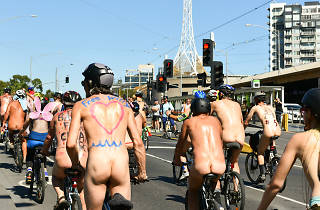 Naked people with slogans painted on them riding towards the arts centre down Swanston Street