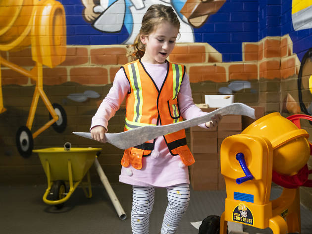 Young girl dressed in high vis playing with construction toys