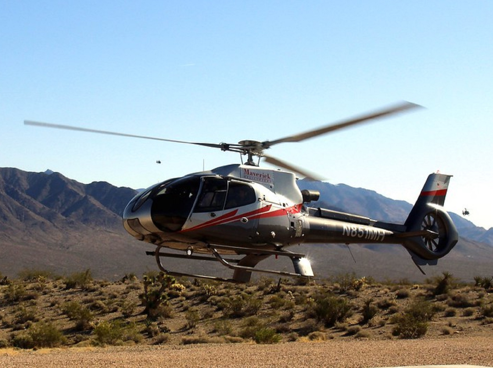 A helicopter lifting off in the desert