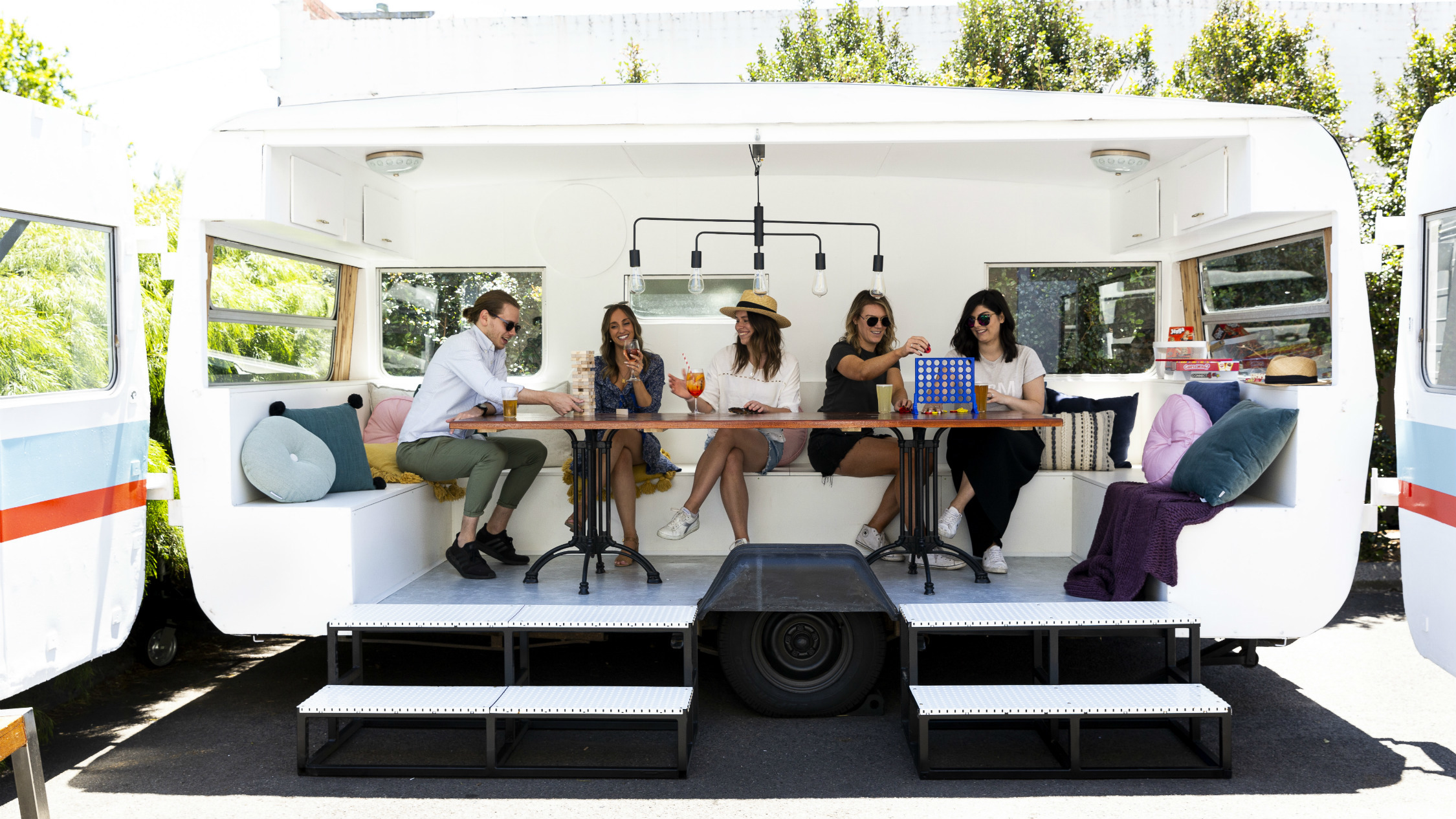People sitting around a table inside a converted caravan