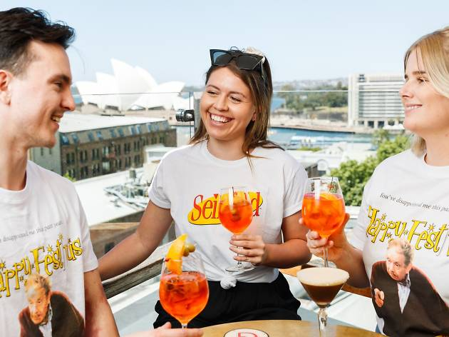 Three people wearing Seinfeld and Festivus themed shirts drink Aperol Spritz.