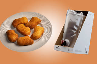 A plate of chicken nuggets and a sack of goon in a half-cut box