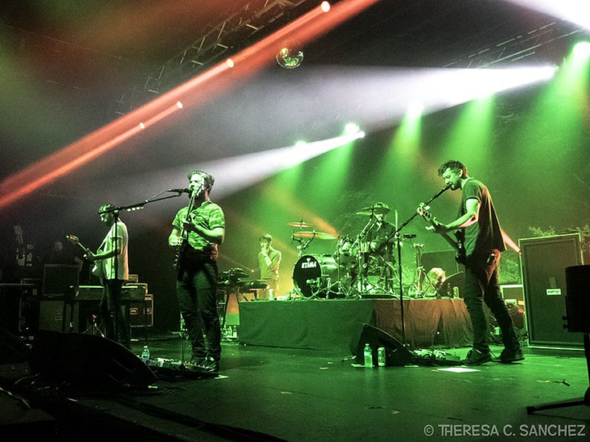 A band on a stage under green and red lights