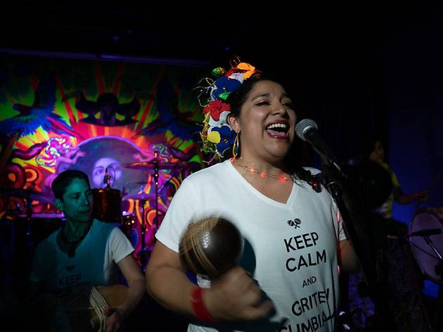 A woman singing with maracas and other bandmates on stage