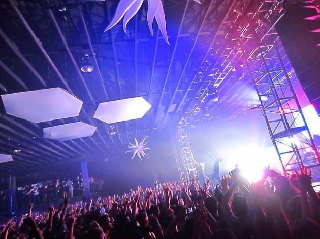 A club with a crowd in front of a stage