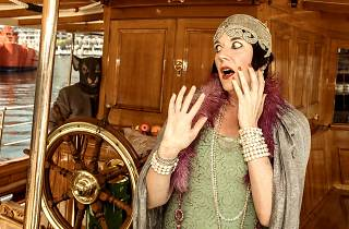 A woman in '20s style dress stands at the wheel of a ship looking shocked.