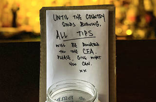 """A tip jar and a handwritten note saying """"until the country stops burning, all tips will be donated the CFA. Please give what you can""""."""