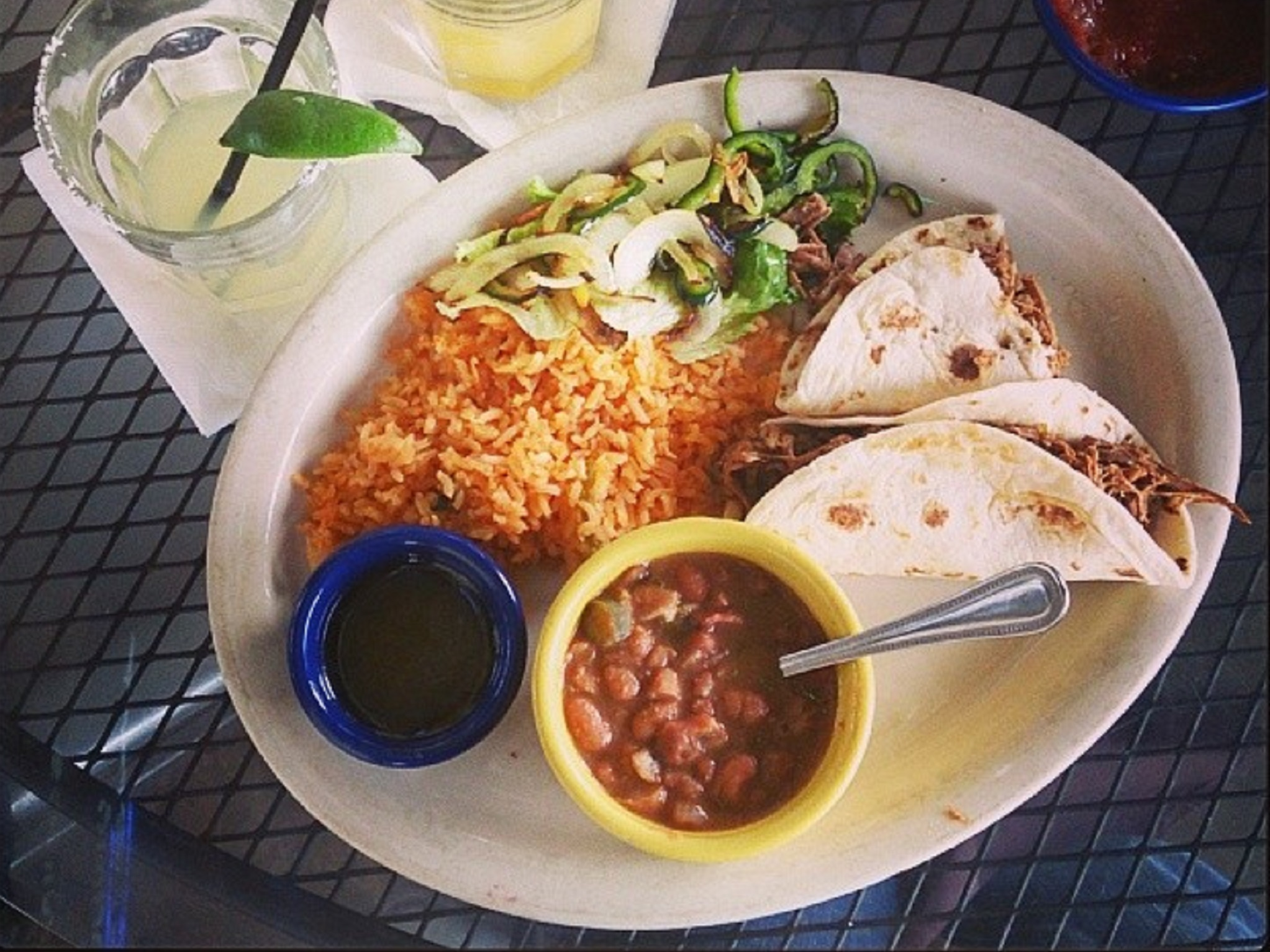 A plate of tacos, rice and beans with a margarita