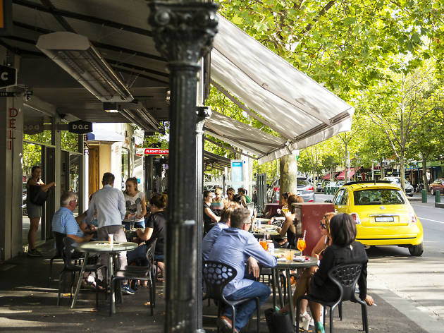 People sitting undercover outside a café on Lygon Street, Melbourne