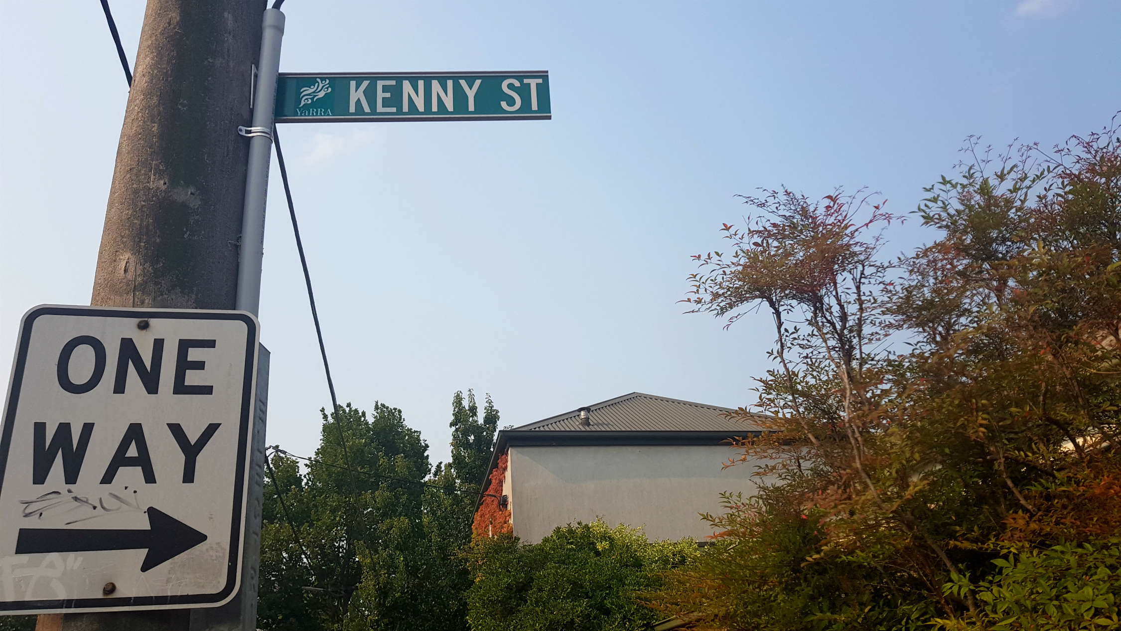 """A street sign with """"Kenny St"""" written on it. A house and tree are in the background"""