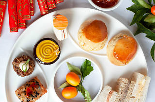 A white plate with lots of small pastries, scones and ribbon sandwiches on it