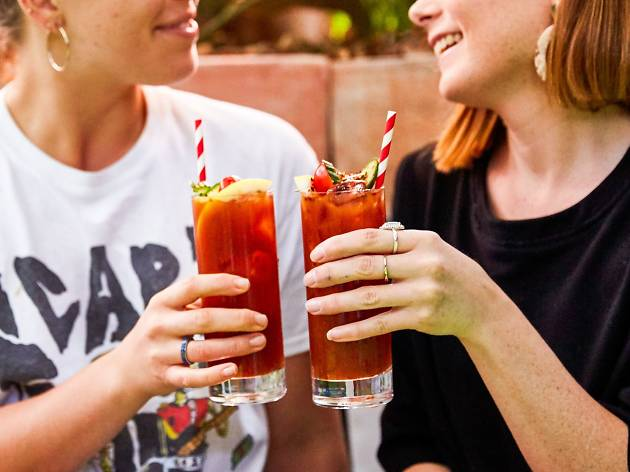Two ladies clinking Bloody Marys at the Norfolk