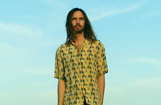 Tame Impala frontman Kevin Parker set against a blue sky