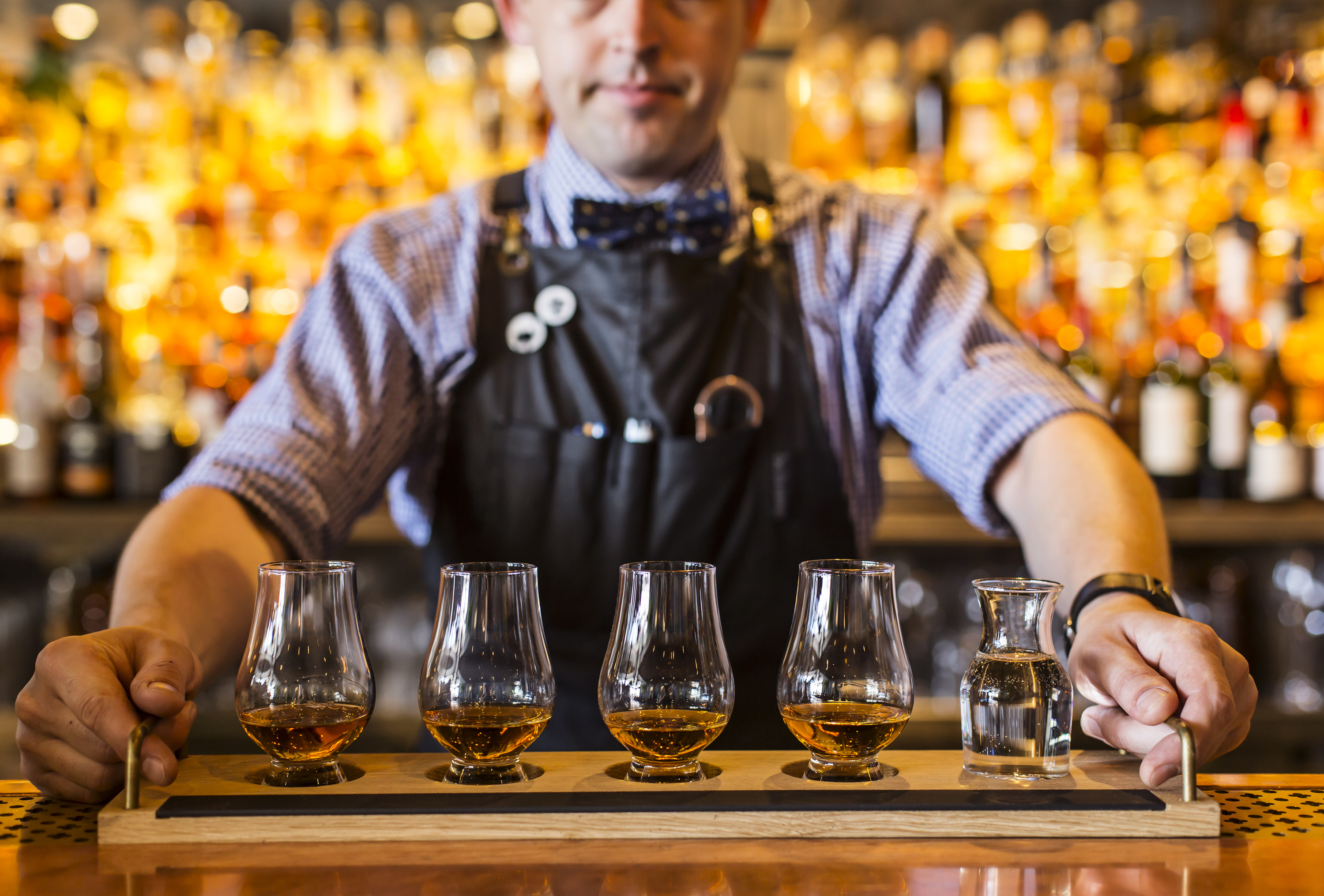 Someone holding a flight of whiskey in tasting glasses
