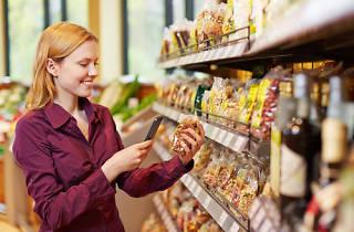 Una noia escaneja menjar en un supermercat