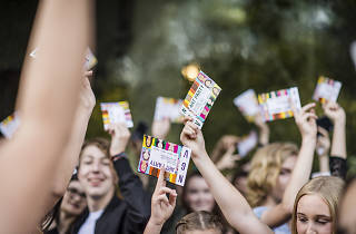 Teenagers dancing with NGV art party flyers