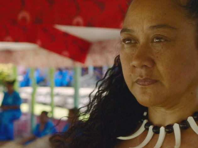 Still from the film 'Vai'; a woman with dark curly hair and a black and white necklace looks stonily into the distance