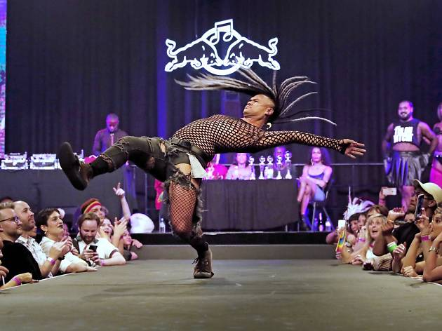 A dancer with long dreadlocks and fishnet undergarments under ripped black jeans is throwing a massive dance move as an audience either side reacts.