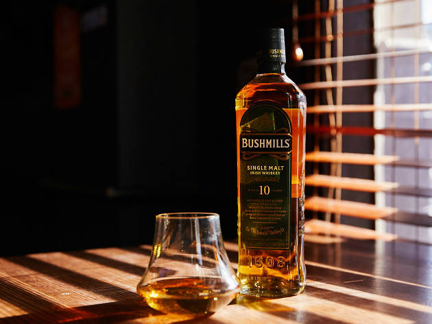 A bottle of Bushmills whiskey and a glass of whiskey next to a window with sunlight streaming in