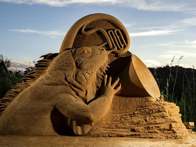 A sand sculpture of an iguana blowing an instrument