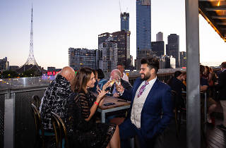 A group of people chatting at Transit Rooftop Bar. You can see the Melbourne skyline and arts centre spire in the background