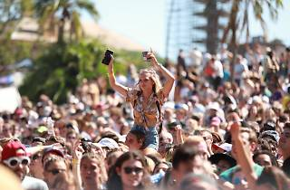 A crowd gathered at Laneway festival, a young woman rides on someone's shoulder.