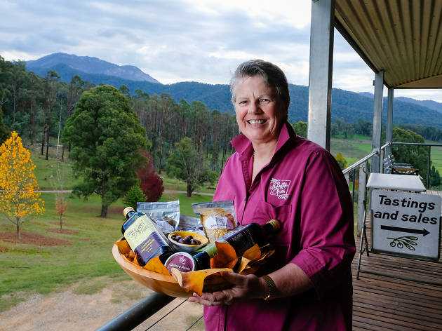 A woman with short hair holding a platter of olive oils and olives on a verandah