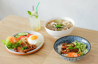 A bowl of soup, a vermicelli noodle dish and a broken rice dish on a table
