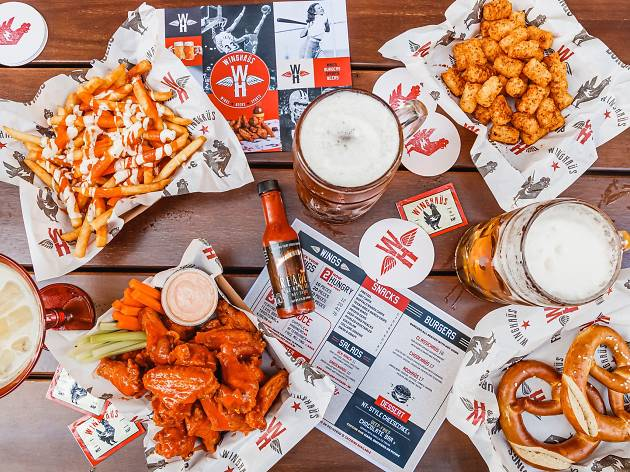 A table with buffalo wings, potato gems, chips, pretzels and beer