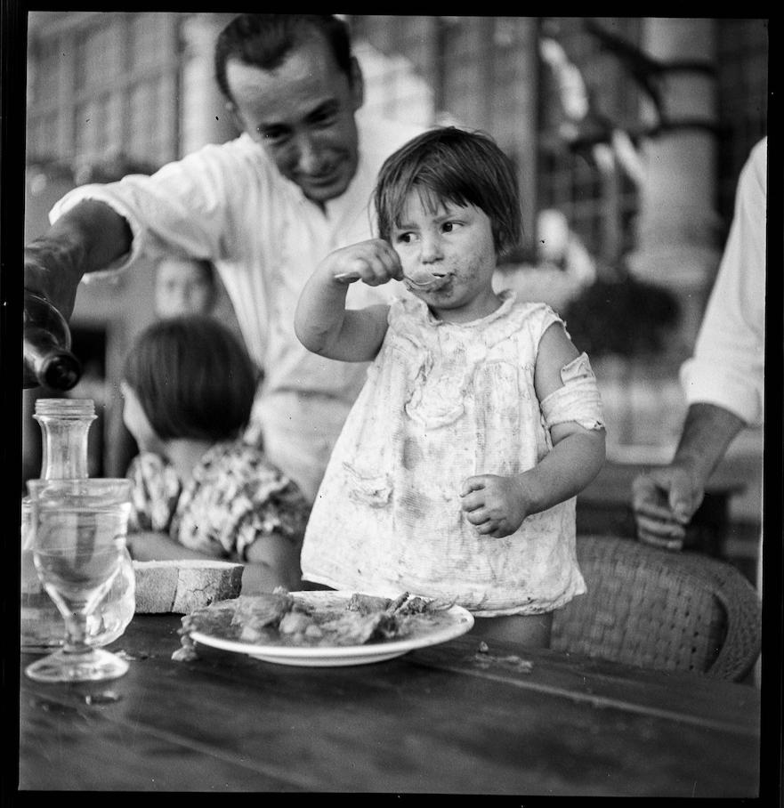 Nena d'uns dos anys menjant al Casino de Sant Sebastià de la Barceloneta. Estiu de 1936.