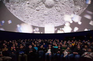 People seated staring up at Planetarium roof