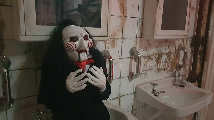 A Jigsaw Killer doll replica from the Saw movie franchise, sitting in a dingy bathroom