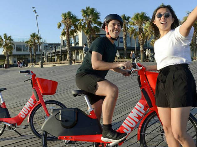Two people on red Jump electric bikes down at St Kilda foreshore