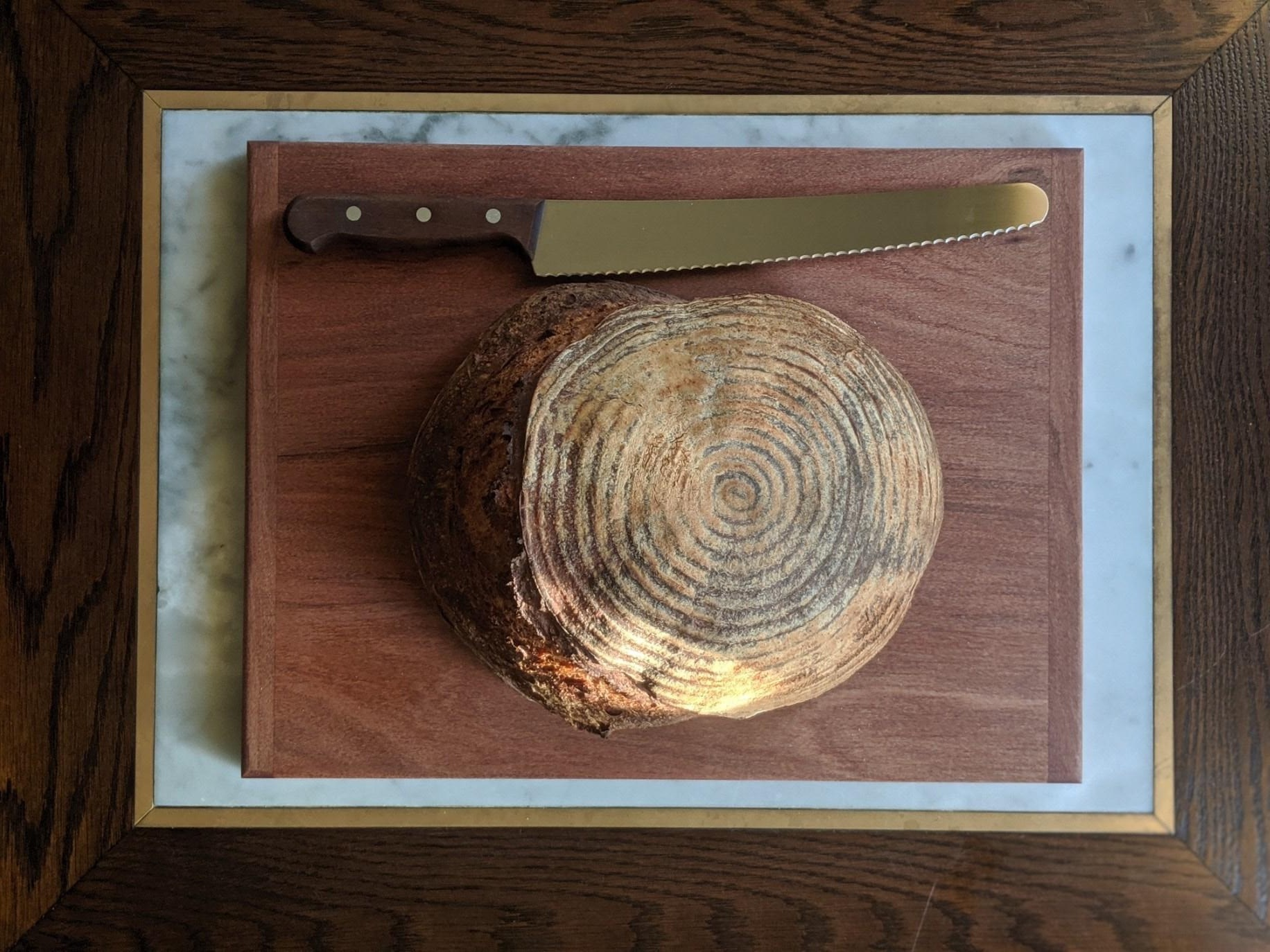 A loaf of sourdough bread on a cutting board with a knife