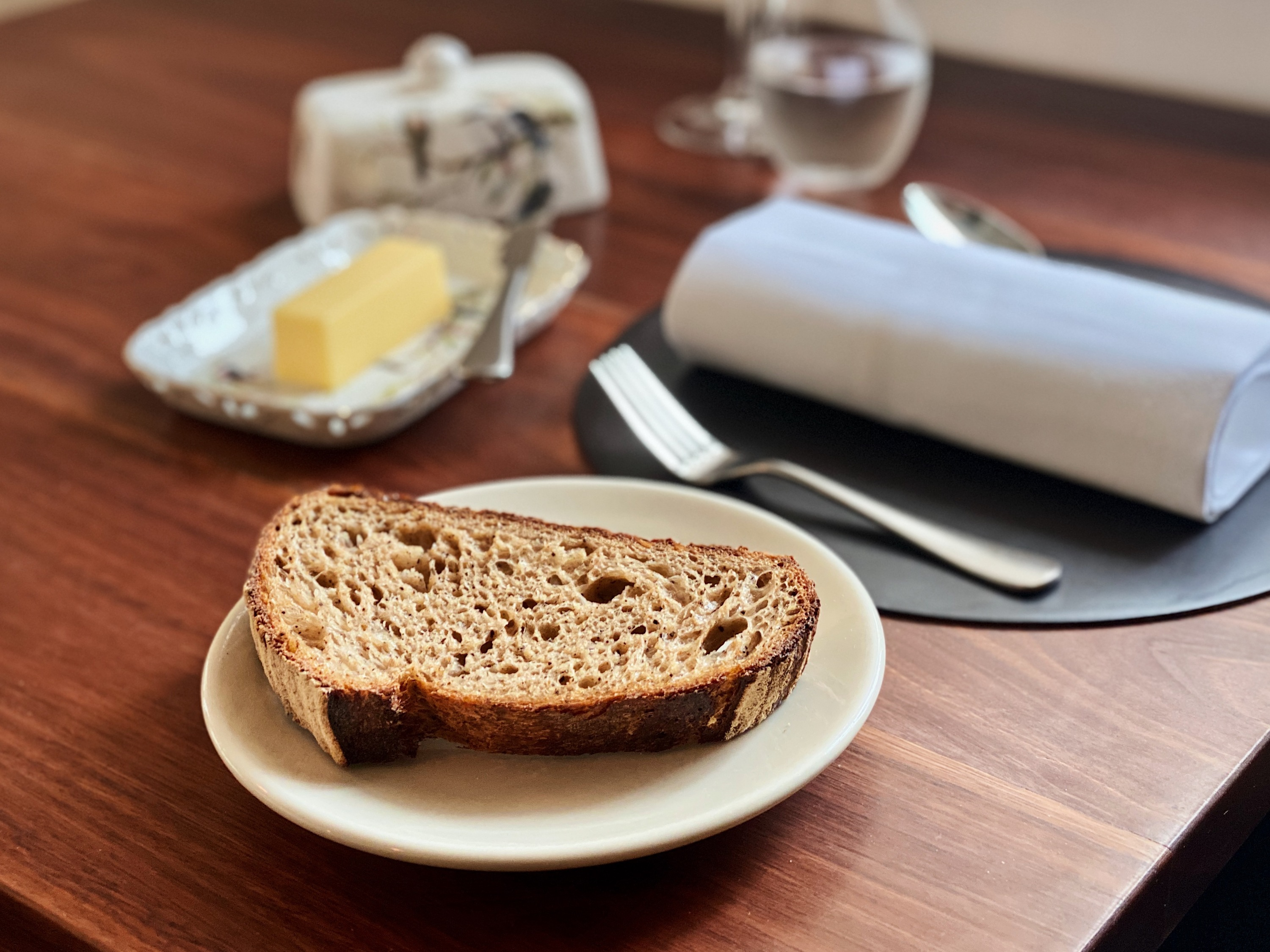 A slice of bread on a set table at Sixpenny