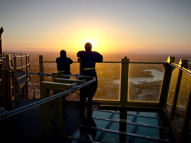 A couple is silhouetted against the sunset as they look out over the city from a great height.