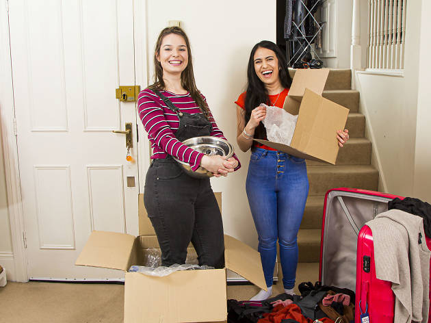 Two women smiling holding cardboard boxes