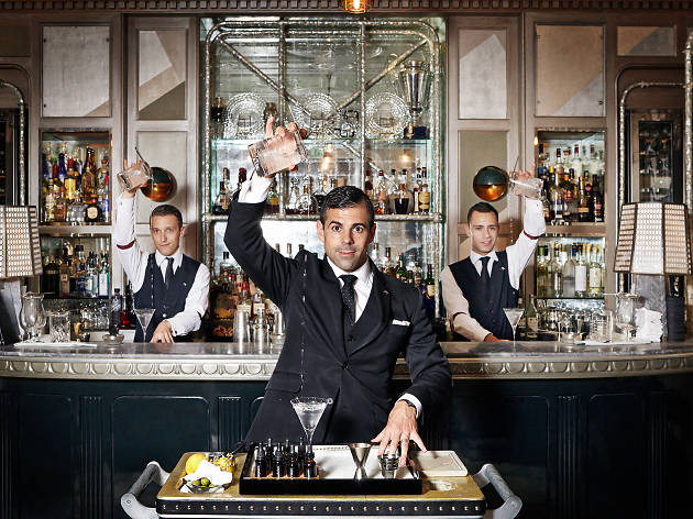 Three bartenders pouring Martinis from up high at the Connaught Bar