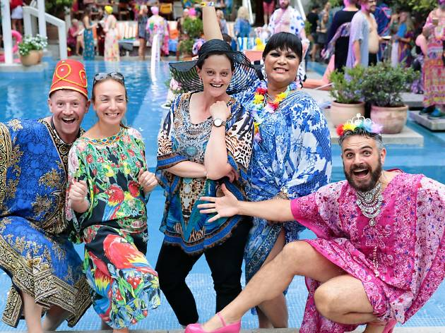 A group of people in bright kaftans pose by a pool.