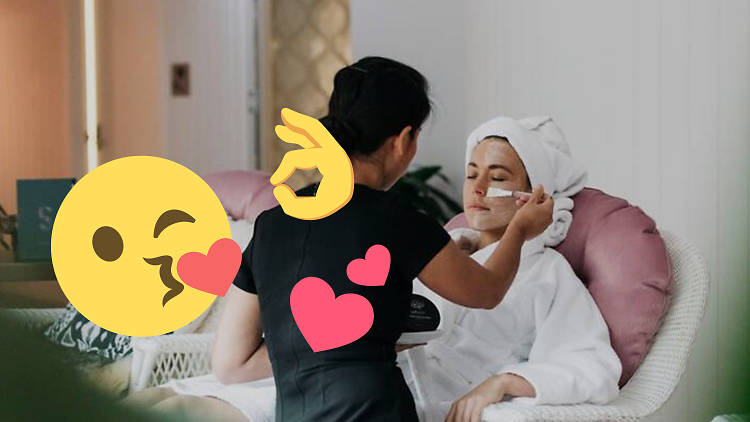 A person wearing a robe is having a face mask applied.