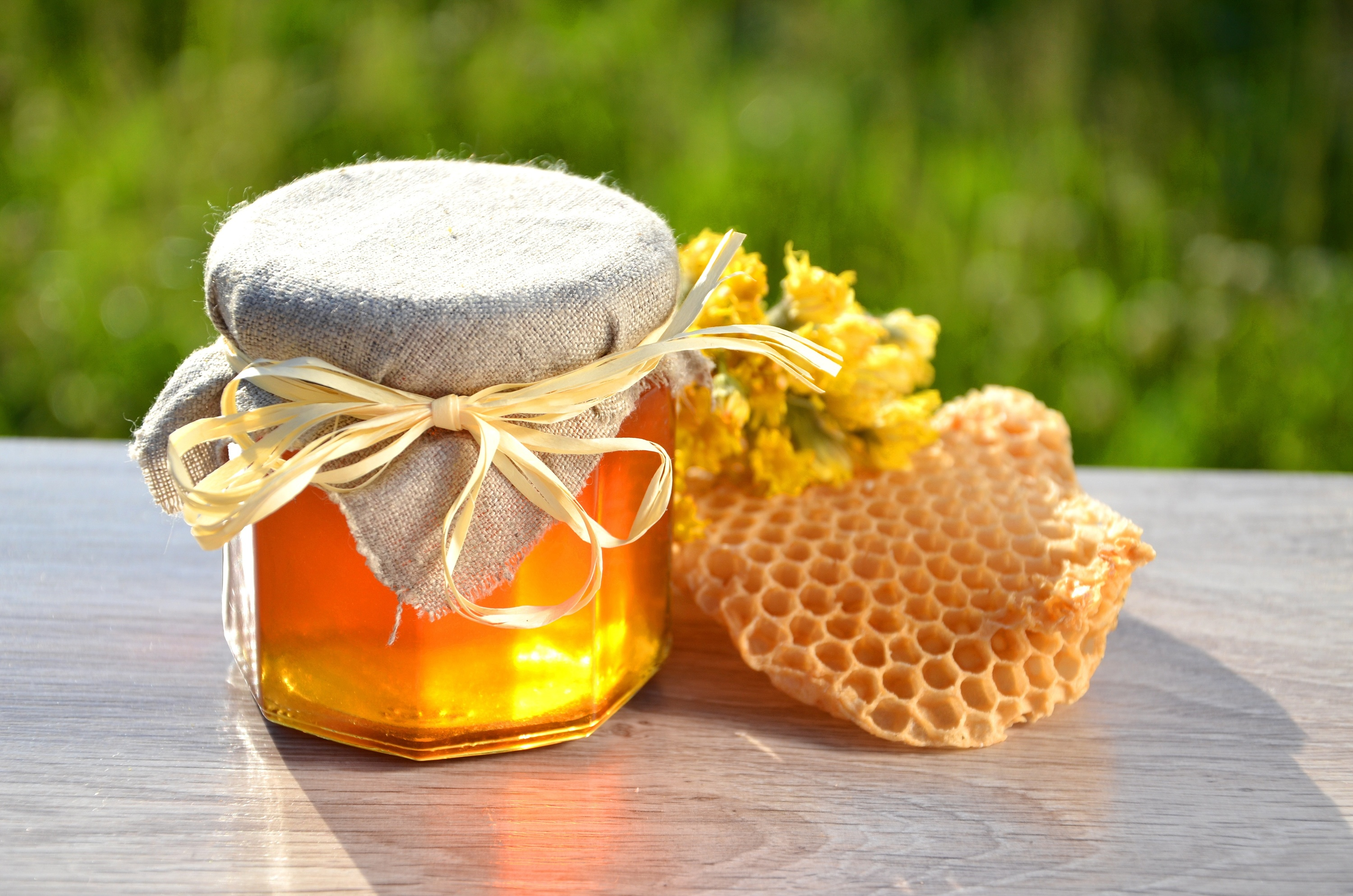 20297150 - jar full of delicious fresh honey piece of honeycomb and wild flowers in apiary