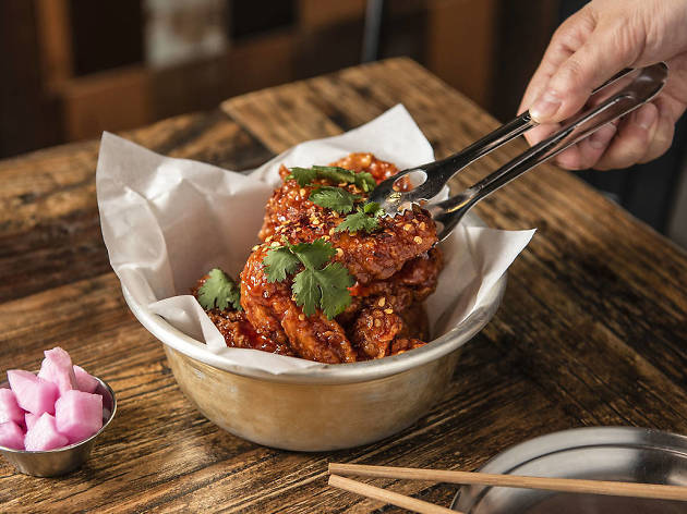 A hand picking up a piece of spicy Korean fried chicken from a bowl